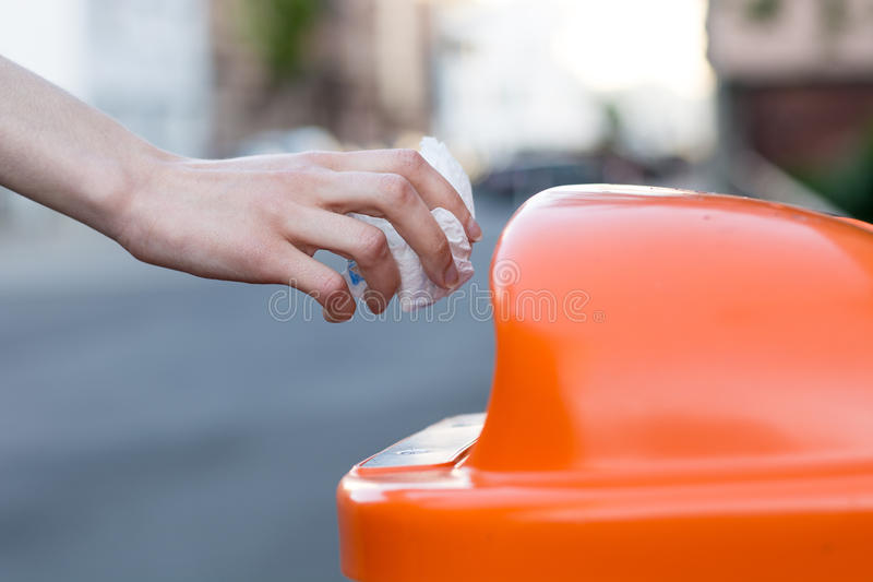 Throwing waste into a an orange trash can in the street. From the side stock images