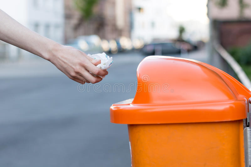Throwing waste into a an orange trash can in the street. From the side royalty free stock photo