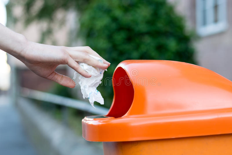 Throwing waste into a an orange trash can in the street. From the side royalty free stock image