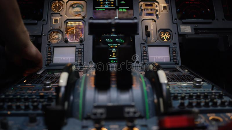 Thrust levers of a twin engined airliner. Thrust levers on the centre pedestal instrument panel. Switches and dials stock image