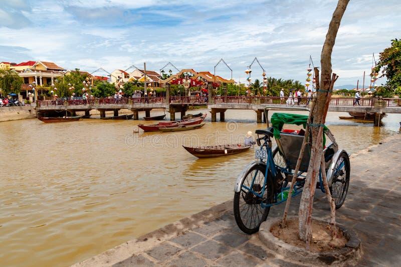 Thu Bon flodstrand i Hoi An, Vietnam, med trehjulingen i förgrunden i dagen royaltyfri fotografi