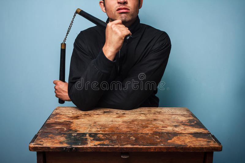 Download Thug At Table With Nunchucks Stock Photo - Image: 32990198