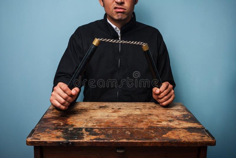 Thug at table with nunchucks stock photography