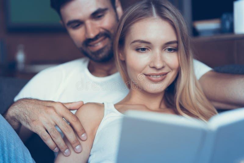 Thuis doorbrengend aardige tijd Het mooie jonge het houden van paar plakken aan elkaar en het glimlachen terwijl vrouw die een bo stock fotografie