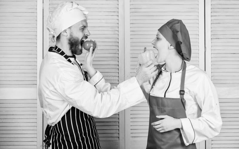 Thuis doorbrengend aardige tijd vegetari?r Eenvormige kok man en vrouwenchef-kok in restaurant gelukkig paar in liefde met stock foto