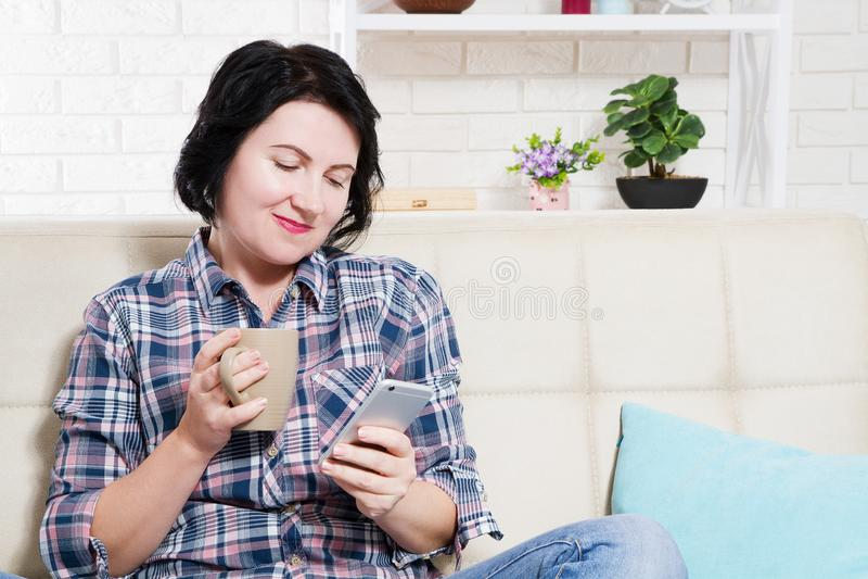 Thuis genietend van koffie Aantrekkelijke jonge het glimlachen vrouwenzitting op bank thuis en de kop en de telefoon van de holdi stock foto