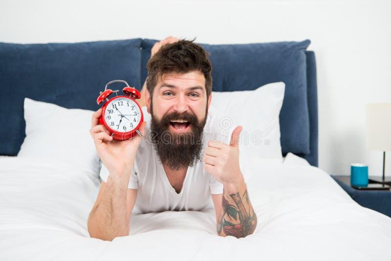 Thuis genietend van vrije tijd gelukkige gebaarde mens hipster met wekker brutale slaperige mens in slaapkamer Mannetje met baard royalty-vrije stock foto's