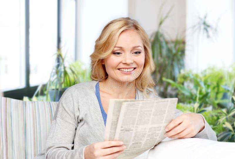 Thuis glimlachend de krant van de vrouwenlezing royalty-vrije stock afbeeldingen