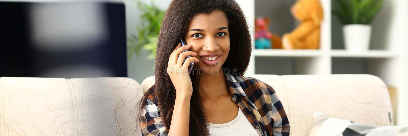 Thuis glimlachend in hand mobiele telefoon van de zwartegreep royalty-vrije stock foto's