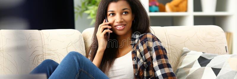 Thuis glimlachend in hand mobiele telefoon van de zwartegreep royalty-vrije stock afbeeldingen