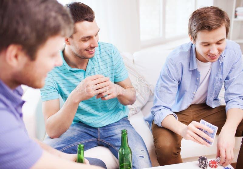 Thuis glimlachend mannelijke vriendenspeelkaarten royalty-vrije stock foto's