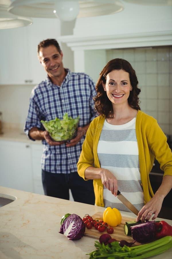 Thuis glimlachend paar hakkende groenten in de keuken stock foto's