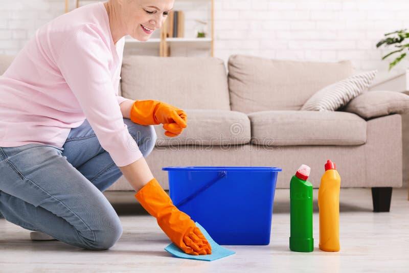Thuis glimlachend rijpe huisvrouwen schoonmakende vloer stock afbeelding