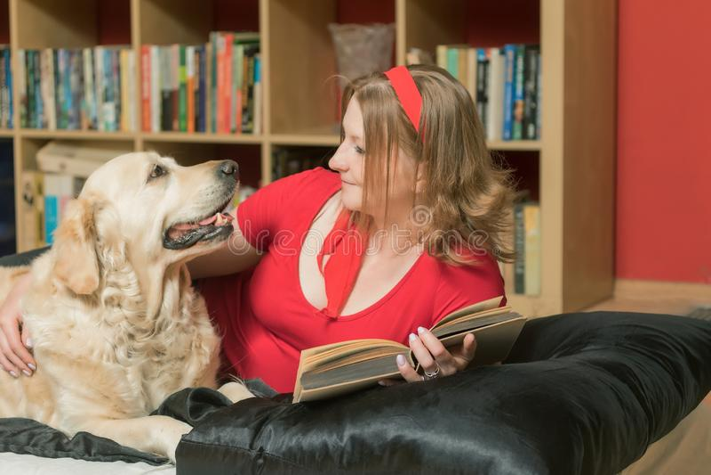 Thuis het ontspannen met een hond en een boek royalty-vrije stock afbeelding
