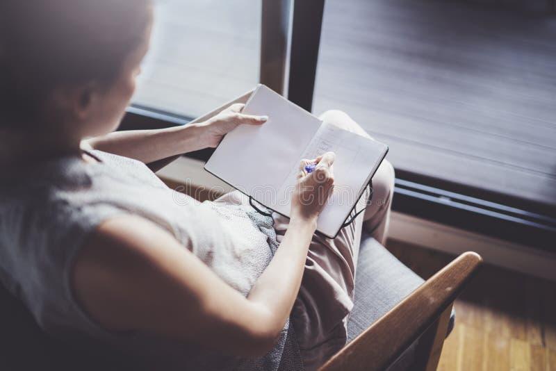 Thuis het werken van concept Jonge bedrijfsvrouw die en nota's schrijven nemen terwijl zitting thuis als comfortvoorzitter ontspa stock afbeelding