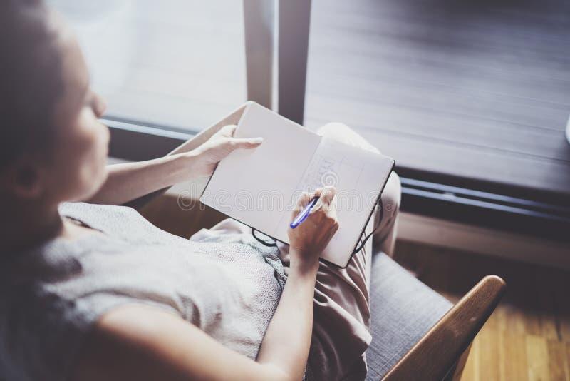 Thuis het werken van concept Jonge bedrijfsvrouw die en nota's schrijven nemen terwijl zitting thuis als comfortvoorzitter ontspa royalty-vrije stock afbeelding