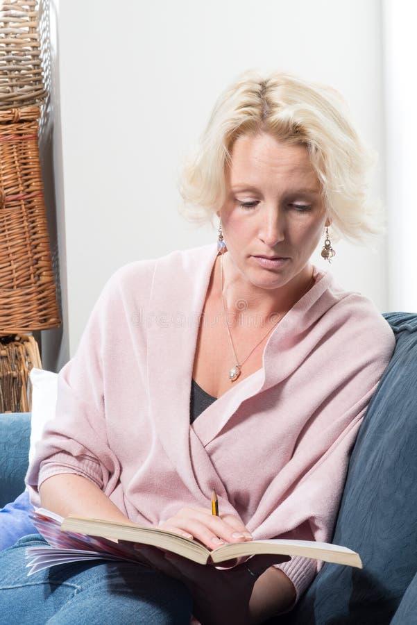 Thuis houdt de terloops Geklede Blondevrouw Boek en Potlood stock afbeelding