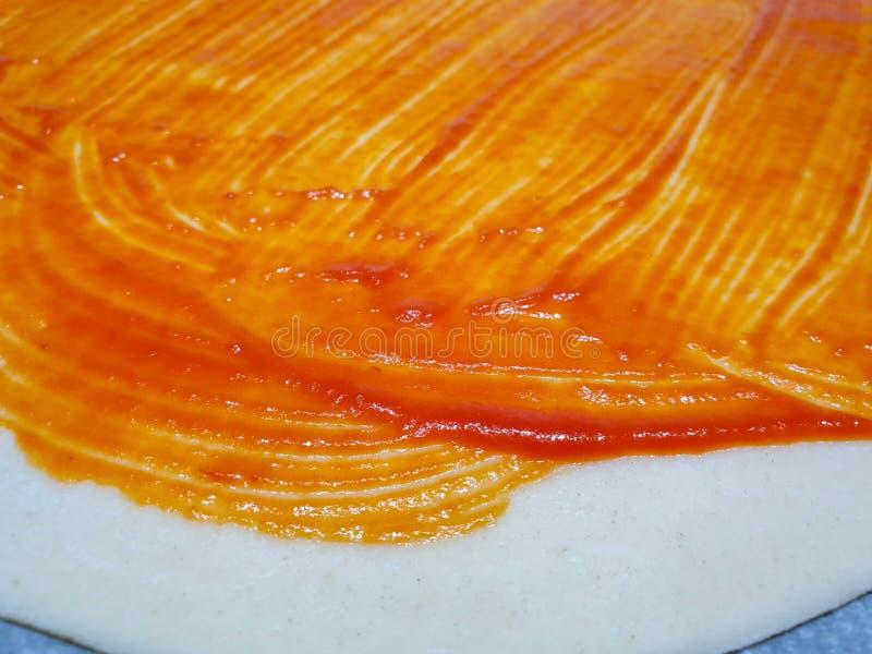 Thuis makend een eigengemaakte pizza U kunt het deeg met de reeds uitgebreide tomaat zien en alvorens de geraspte kaas toe te voe stock foto