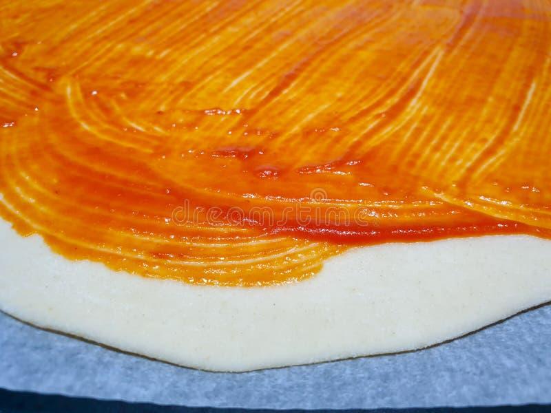 Thuis makend een eigengemaakte pizza U kunt het deeg met de reeds uitgebreide tomaat zien en alvorens de geraspte kaas toe te voe royalty-vrije stock afbeelding