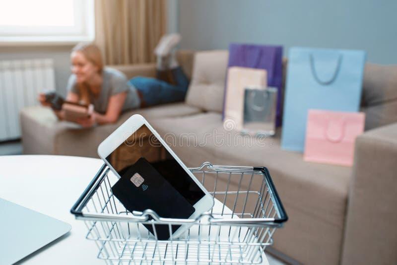 Thuis online winkelend Creditcard en smartphone op een achtergrond van een vrouw met het winkelen zakken royalty-vrije stock foto's