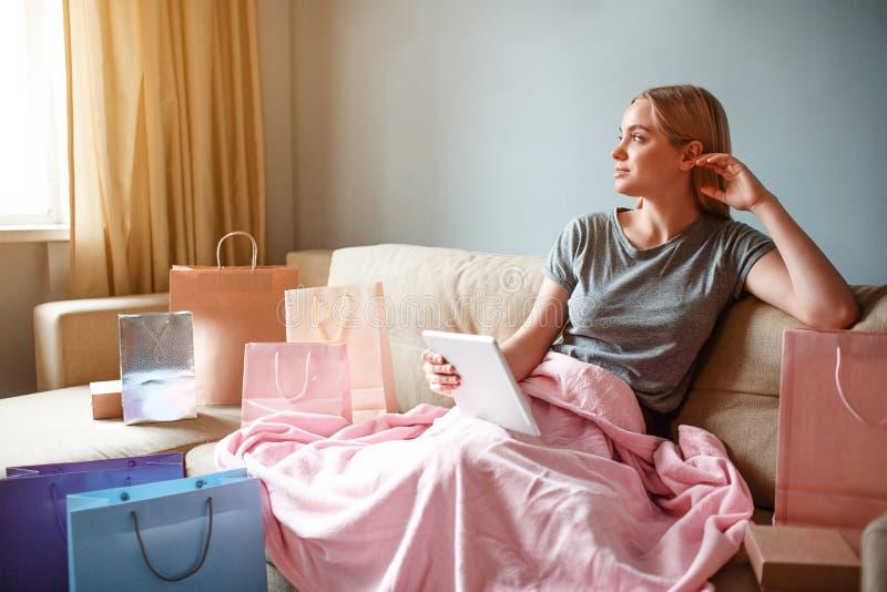 Thuis online winkelend De jonge blondevrouw met tablet denkt over goederen terwijl het zitten met deken op een bank stock foto's