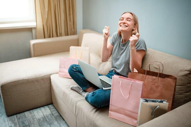 Thuis online winkelend De jonge gelukkige vrouw met wacht op begin van zwarte Vrijdag terwijl het zitten op een bank met royalty-vrije stock afbeeldingen