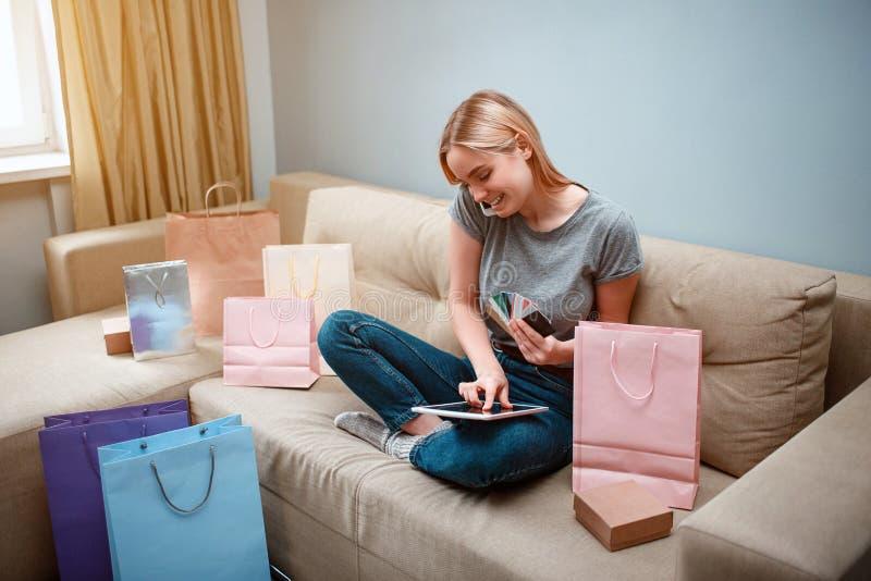 Thuis online winkelend De jonge glimlachende klant met tablet en creditcards geeft tot door smarthphone in online winkel opdracht stock afbeelding