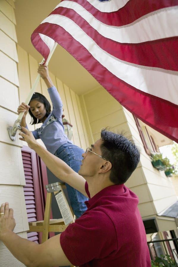 Thuis opheffend de vlag