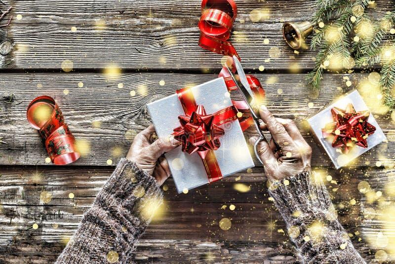 Thuis voorbereidend een Nieuwjaar` s gift Kerstmisklok, Kerstmisdecoratie, gouden sneeuwvlokken, dalende sneeuw stock afbeeldingen