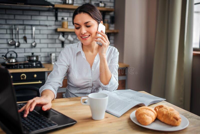 Thuis zit de vrolijke vrouw van Nice bij lijst en het werk Zij die bij laptop toetsenbord en de bespreking op telefoon typen Haar royalty-vrije stock afbeeldingen