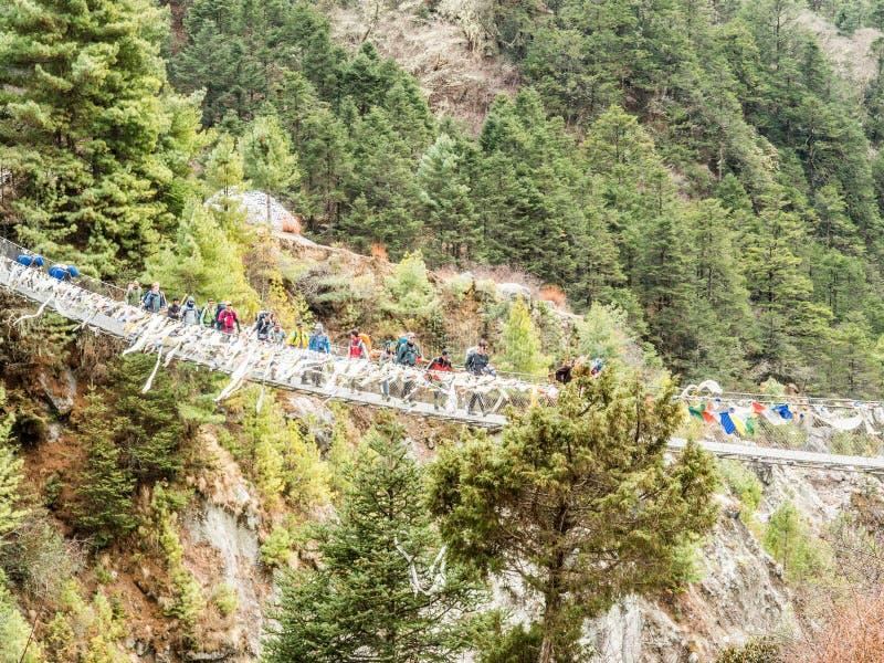 Thukla, Népal 04/13/2018 : Trekkers croisant le pont sur l'itinéraire au camp de base d'Everest photographie stock