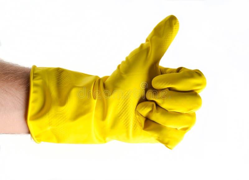 Thumb вверх в желтой резиновой перчатке изолированной на белизне, man& x27; рука s стоковые изображения rf