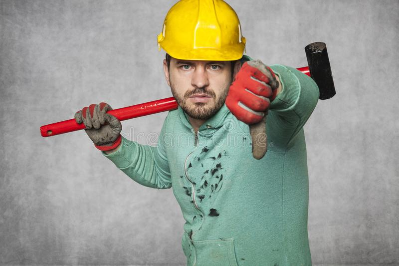 Thumb down and unhappy worker`s face. Protective helmet on the head royalty free stock photos
