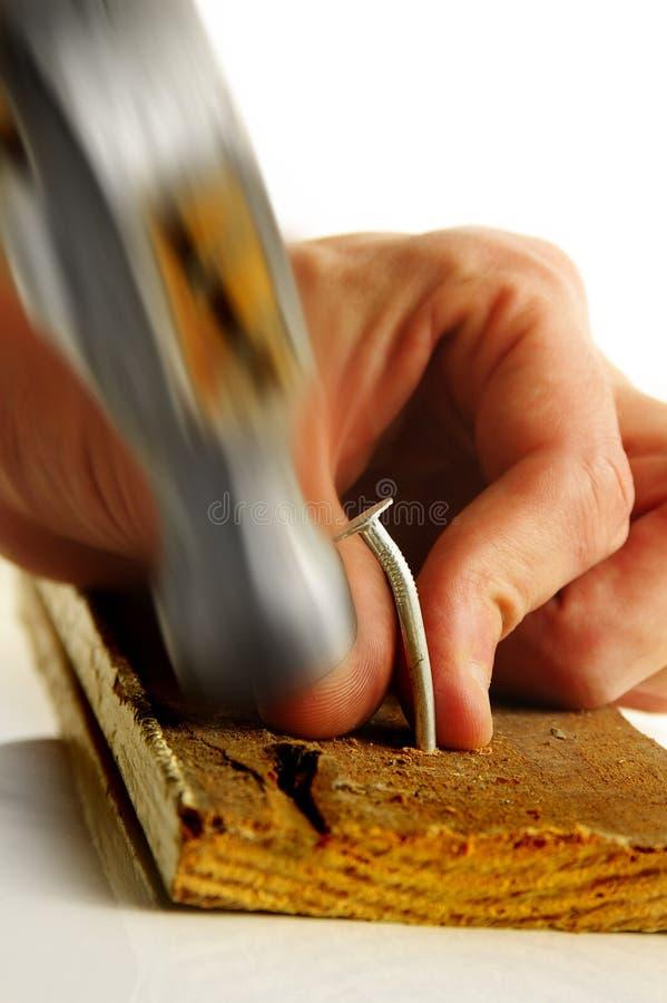 Thumb smash. Hammer smashing a man's thumb stock photo