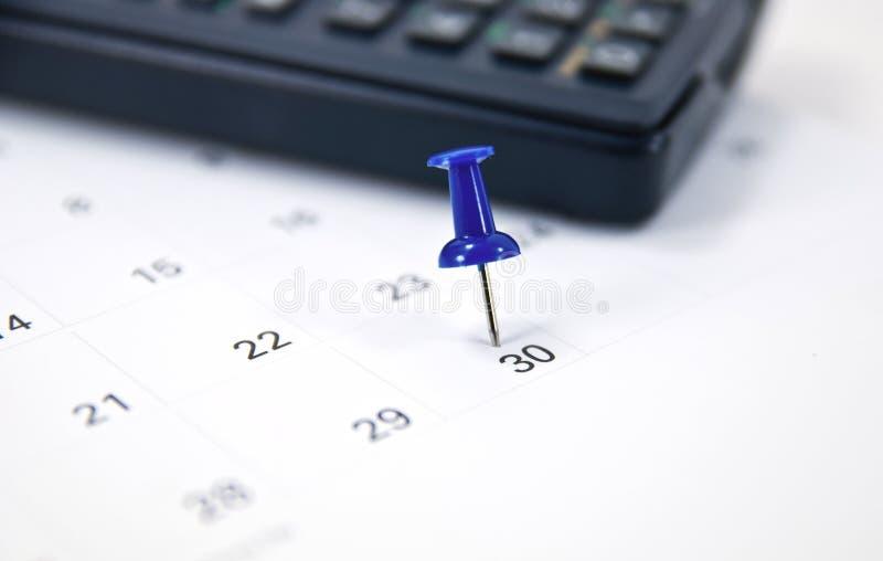 Thumb tack on calendar. Blue thumb tack on calendar royalty free stock photography