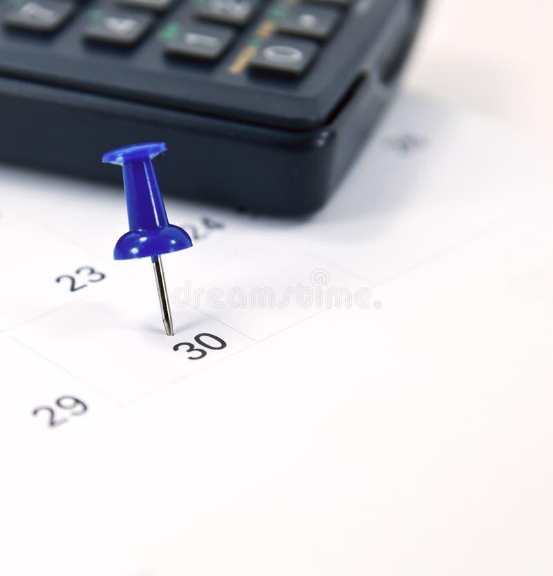 Thumb tack on calendar, salary day. Blue thumb tack on calendar page for salary day royalty free stock photo