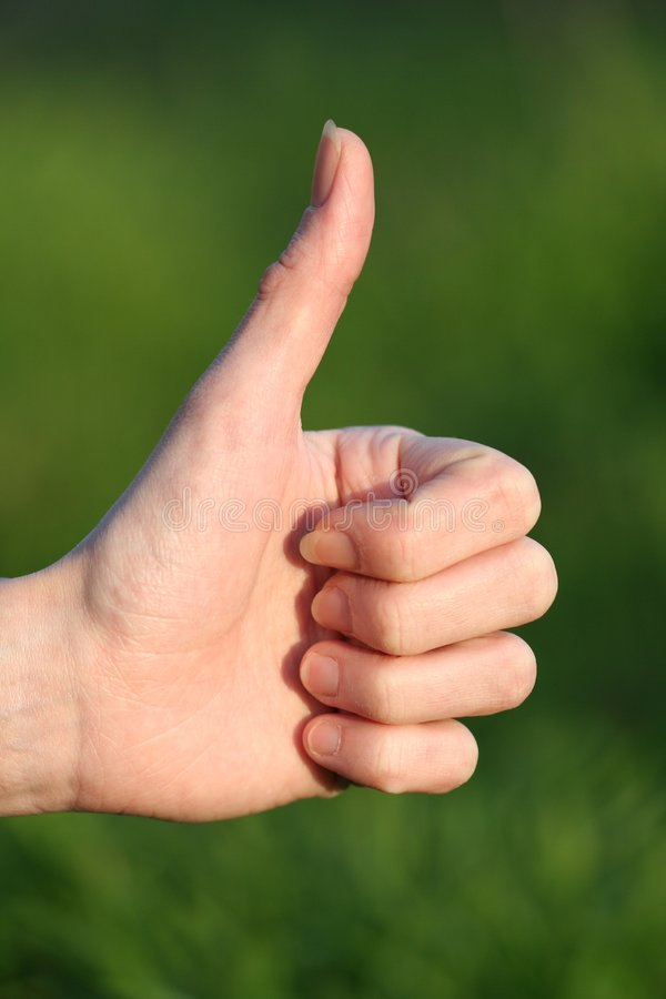 Thumb up. Girl thumb up detail on green background royalty free stock photography