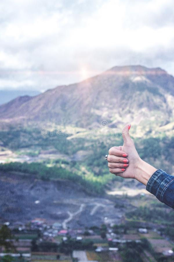 Thumb up on a beautiful mountain background with sunlight. Volcano Batur, Bali island. Indonesia royalty free stock photo