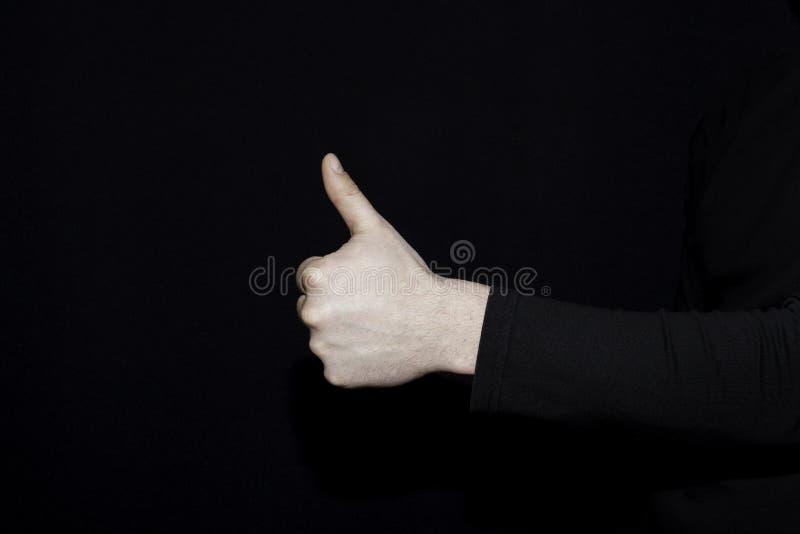 Thumb up on dark background stock photo