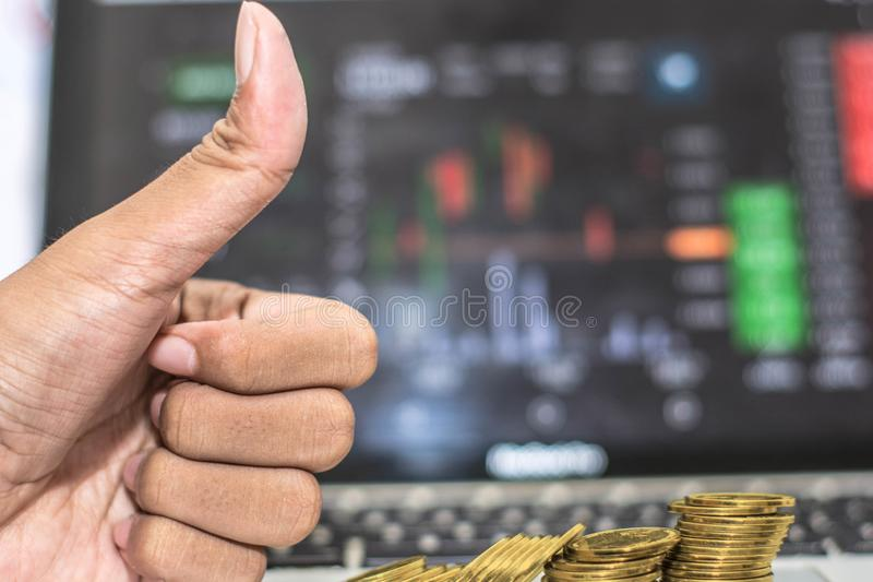 Thumb up hand and coin with monitor shows trading traffic, Bitcoin minning. Close up of thumbs up hand with gold coin, bitcoin, and stock trading photo stock images