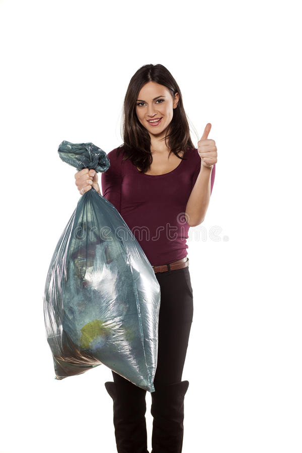 Thumb up. Happy young woman holding garbage bag and showing thumb up royalty free stock photography