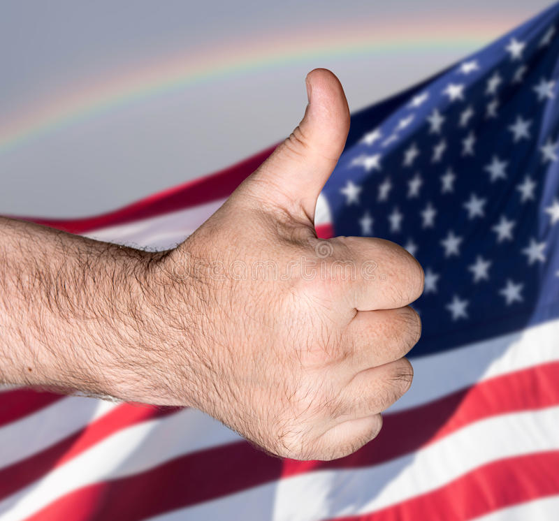 Thumb up sign against of USA flag. Patriotic concept. Thumb up sign against of United States of America flag stock photos