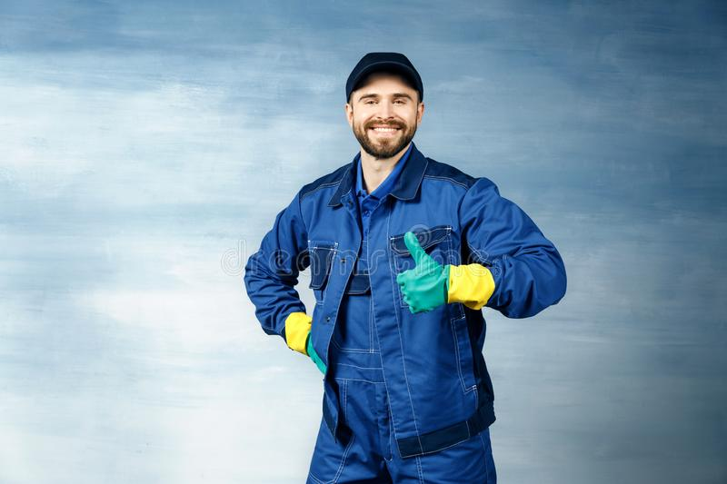 Thumb up. Young handsome man with a beard in a blue working uniform for cleaning rooms smiles isolated royalty free stock photos