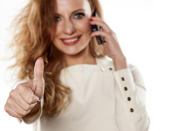 Thumb up. Young woman talking on the phone and showing thumb up royalty free stock photography