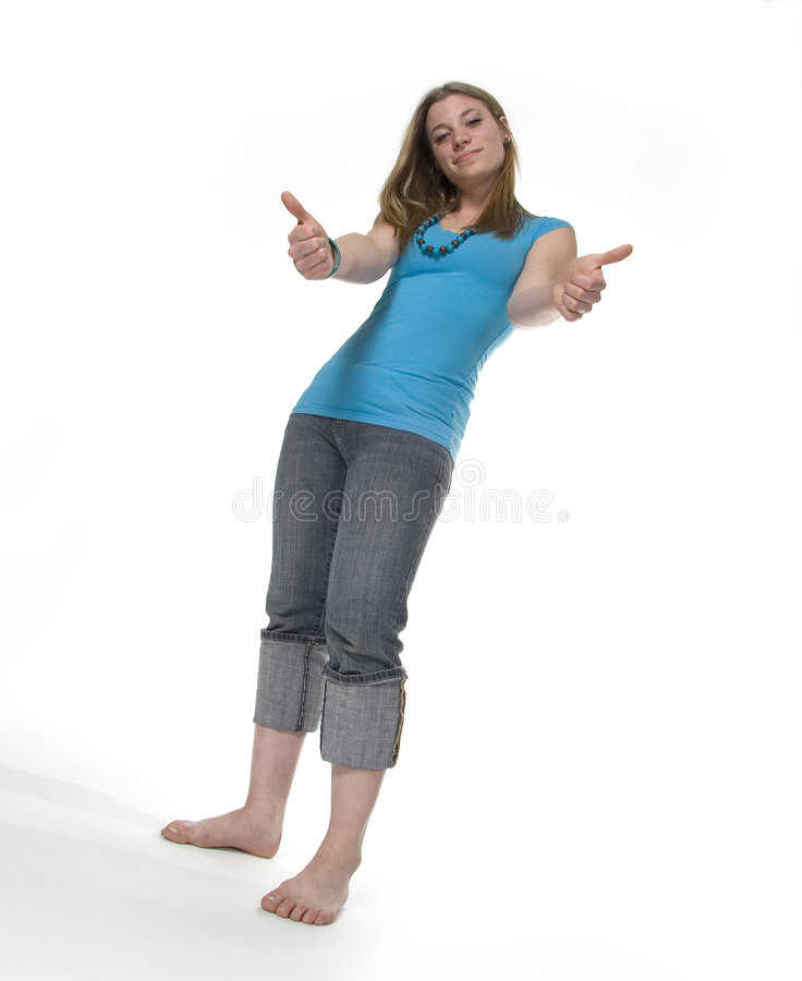 Thumbs up. Teenage girl giving thumbs-up gesture.isolated on white. shot from low angle. full length stock image