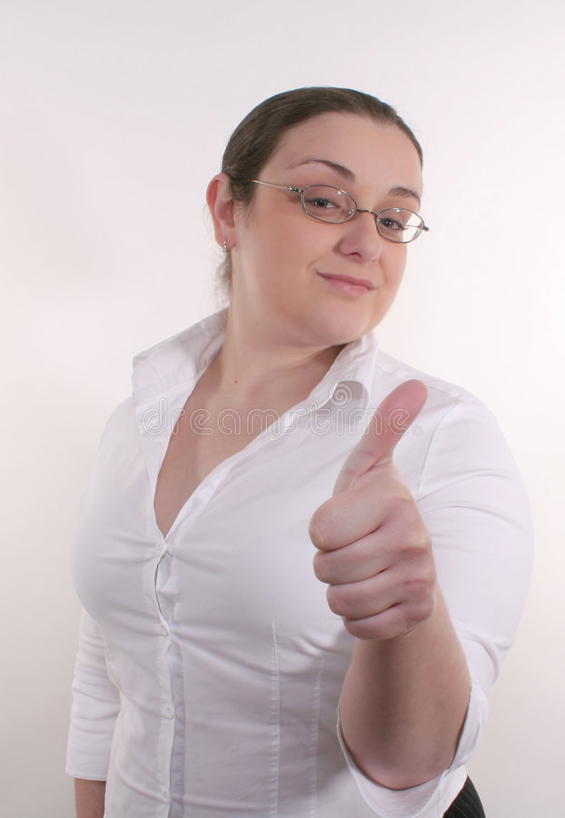 Thumbs Up #2. A young business woman with glasses wearing a white button-down giving a thumbs up royalty free stock image