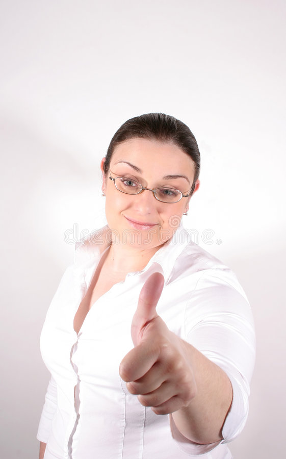 Thumbs Up. A young business woman with glasses wearing a white button-down giving a thumbs up stock image