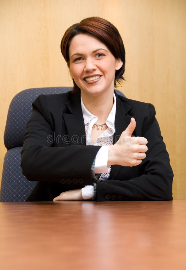 Thumbs up!. Happy business woman in a boardroom table stock images