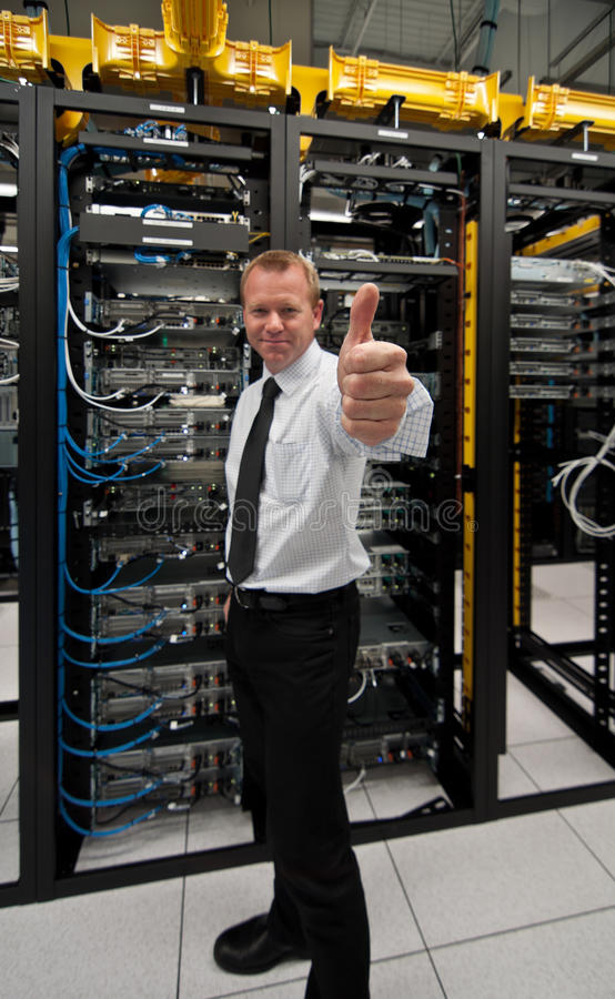 Thumbs up. A Cheerful network administrator posing a thumbs-up in front of data center server racks royalty free stock photo