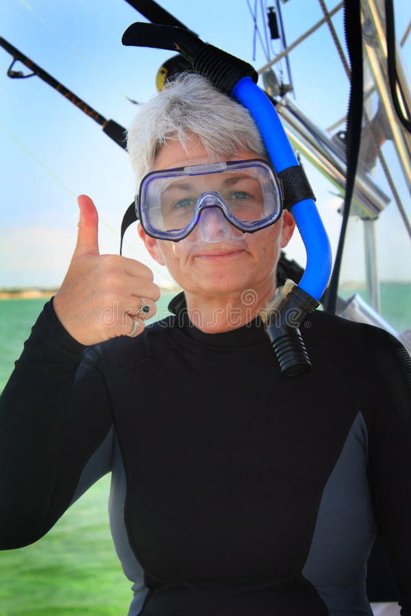 Thumbs up. And all ready to snorkel. A cute senior lady with white hair is suited up with wet-suit, head mask and snorkel gear ready to dive royalty free stock photo
